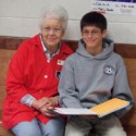 Foster grandparent volunteer helping child with homework