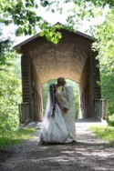 Wedding couple posing in front of covered bridge at Deerfield Nature Park